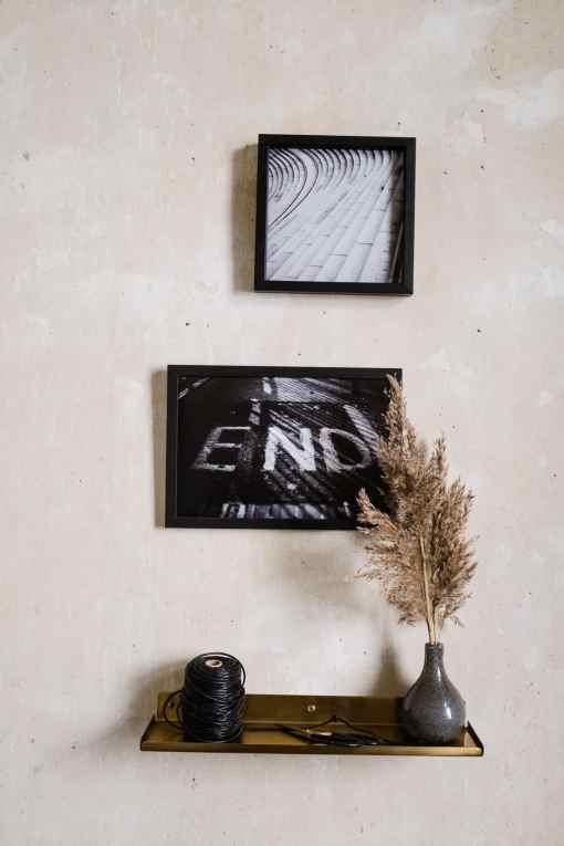 Zwei Bilder an verputzter Wand, Messingregal mit Vase und Trockenblumen und schwarzem Packband