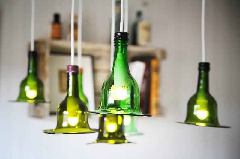 Lampor av gröna vinflaskor, hängandes i kluster.