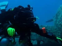 rebreather diver hovering next to a small airplane