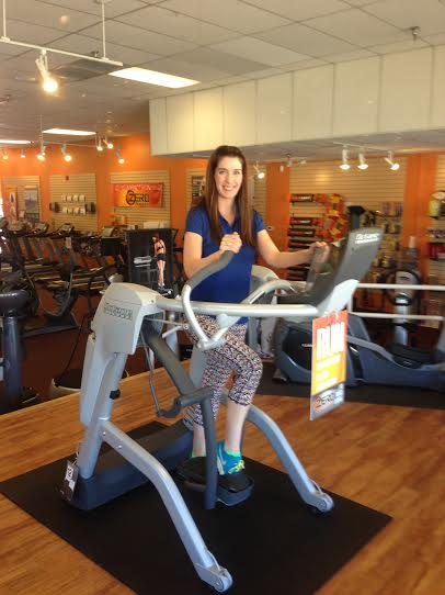 """At Home Fitness store manager Jaime Janman stands on the brand new Octane Zero Runner. The Michigan native said she enjoys working for AHF because the company """"really cares about its employees and customers."""""""