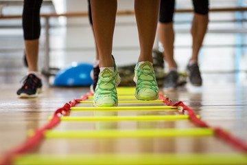 Photo d'athlètes qui font de la préparation physique grâce à une échelle de rythme