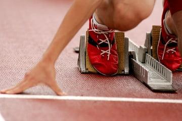 Photo d'un athlète dans les starting block sur la ligne de départ. Il porte des chaussures rouges