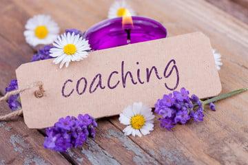Photo d'une table en bois avec des marguerites et des fleurs violettes. Il y a une étiquette en carton avec l'inscription Coaching.