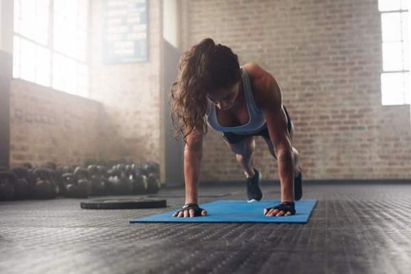 Photo d'une femme brune sportive et musclée. Elle fait du gainage abdominal en faisant la planche. Dans la salle de fitness il y a des haltères et un disque