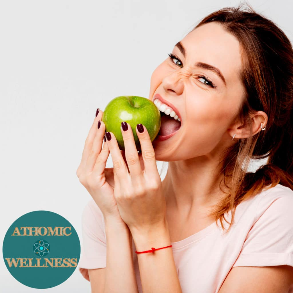 Photo d'une jolie et jeune femme aux yeux verts croquant dans une pomme verte