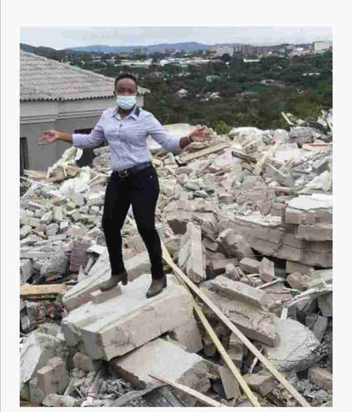 Lady whose boyfriend demolished the house he built for her after dumping him poses on the debris
