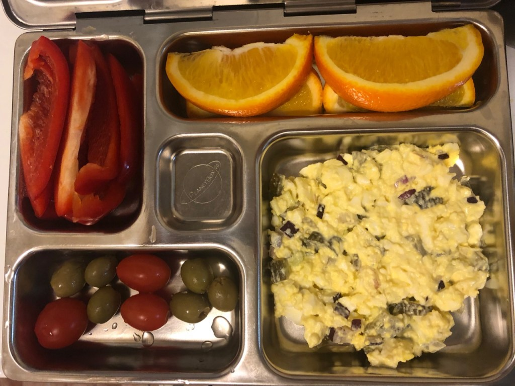 Egg salad / cherry tomatoes and olives / orange slices / red bell pepper