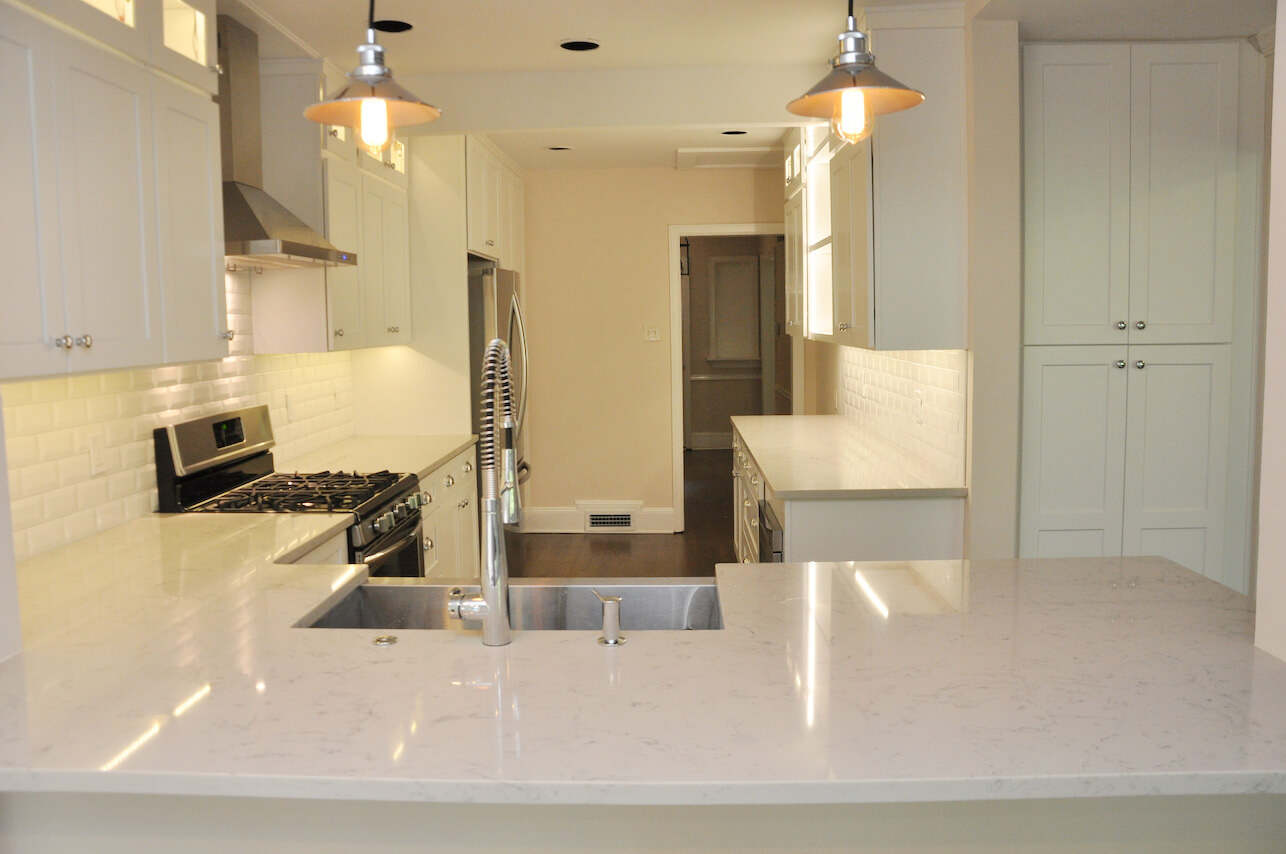 white sleek and fresh kitchen with white tile and white marble counter tops
