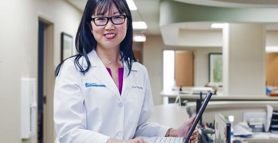 Joyce C. Peji, MD smiling at computer