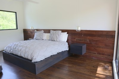 The platform bed is made of stained walnut veneer