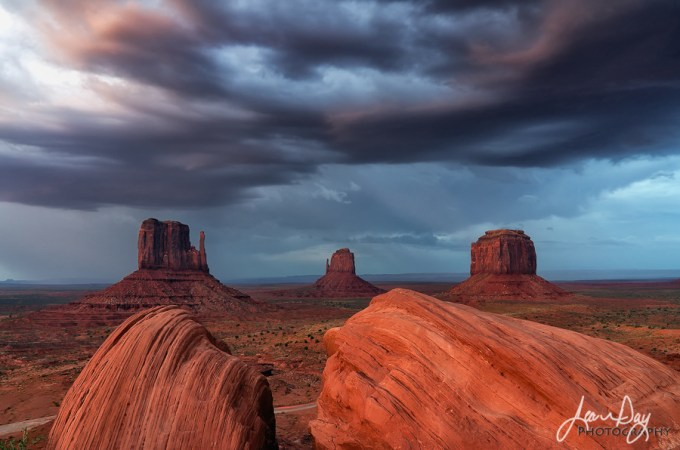 With just enough light coming through the clouds, the final glow of sunset shines on Monument Valley.