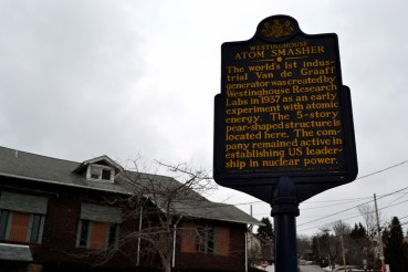 Pennsylvania State Historical marker for the atom smasher, dedicated 2010. The building in the background is the former community building/cafeteria of the Research Labs. © Marni Blake Walter.