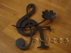 イニシャルTとト音記号に四つ葉のクローバーを組み合わせてデザインしたおしゃれで人気のロートアイアン風アルミ製オーダー妻飾りの写真