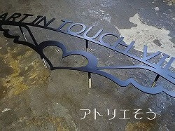 アトリエそうデザイン制作のオーダーメイド妻飾り看板です。HEART IN TOUCHの文字のロートアイアン風ステンレス製看板です。