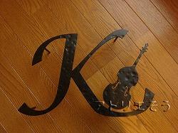 イニシャルK+コントラバス妻飾り 。ロートアイアンで叩いて凹凸を付けた妻飾りです。