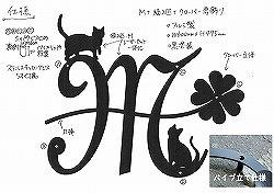 イニシャルMと猫と四葉のクローバーを組み合わせてデザインしたおしゃれで人気のロートアイアン風アルミ製オーダー妻飾りの写真