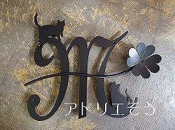 イニシャルMと猫と四葉のクローバーを組み合わせてデザインしたおしゃれで人気のロートアイアン風アルミ製オーダー妻飾りの設置写真