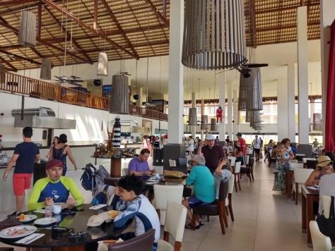 #PraCegoVer Audiodescrição: fotografia interna de restaurante amplo, com várias mesas e teto alto. Muitas pessoas circulando e sentadas