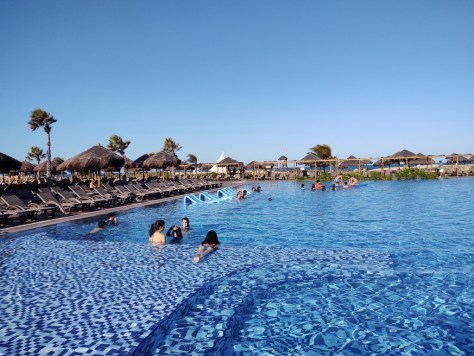 #PraCegoVer Fotografia com grande piscina azul rodeada por espreguiçadeiras e coqueiros. Praia ao fundo. Pessoas na piscina conversando. Céu azul
