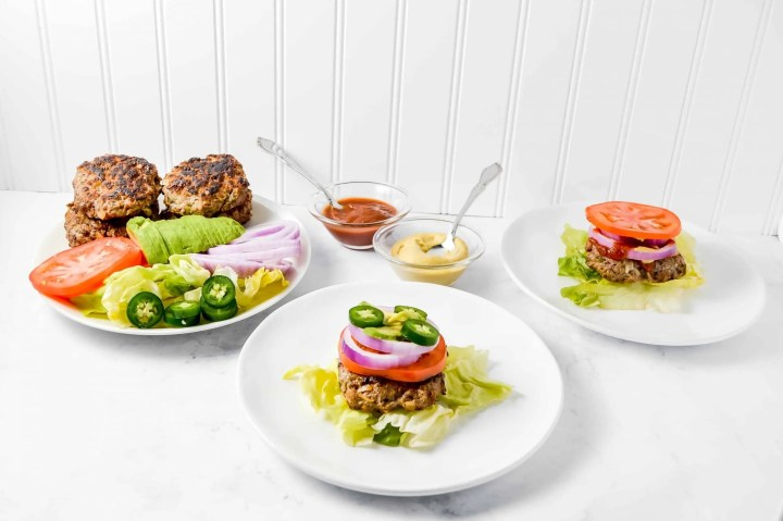 image is o top view of the savory Ranch Burger on a bed of lettuce on a white place. On the burger there is tomato, purple onion and jalapeño. In the background are bowls of ketchup and mustard. To the top right is a plate of lettuce, tomato, onion, savory ranch burgers and avocado. To the top right is a bowl of ketchup and a bowl of mustard. https://www.atwistedplate.com/savory-ranch-burger/