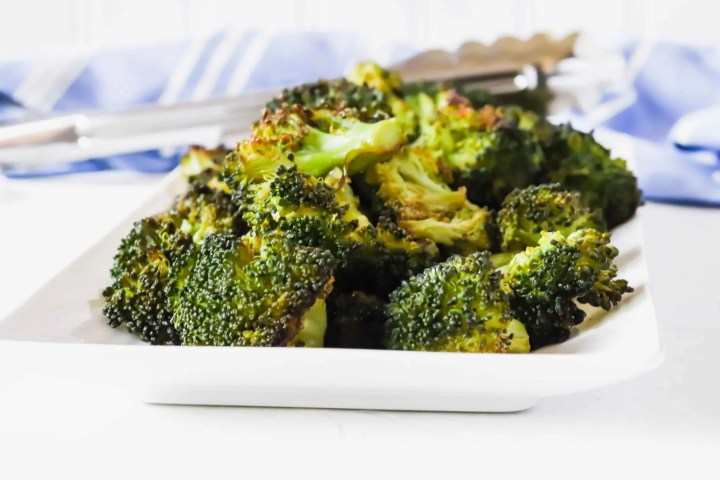 """image is """"blackened"""" broccoli on a angled white rectangle dish with cut up broccoli in the background. www.atwistedplate.com/blackened-broccoli/"""