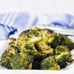 """Image of """"blackened"""" broccoli on a angled white rectangle dish with cut up broccoli in the background. www.atwistedplate.com/blackened-broccoli/"""