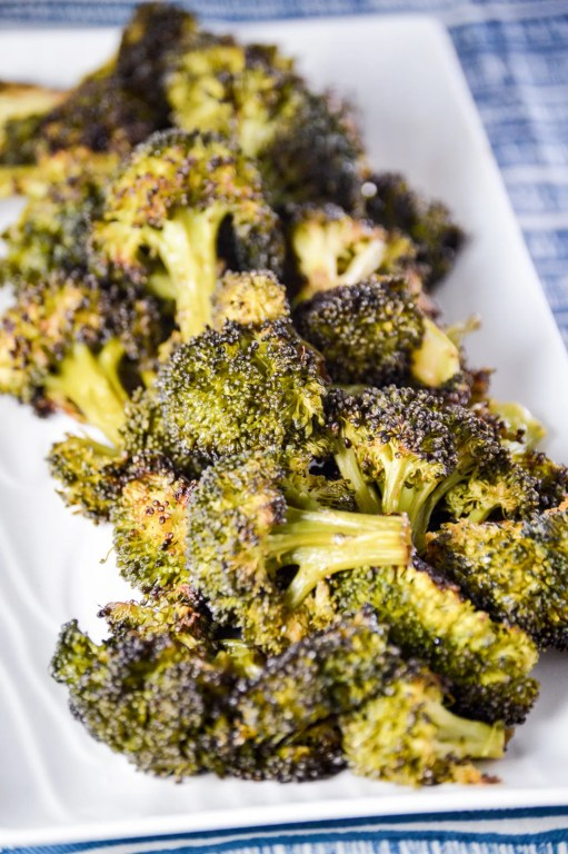 blackened broccoli  on an angled white rectangle dish on a blue and white towel.  www.atwistedplate.com
