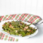 """Pinterest Image for Perfectly Roasted Potatoes. Top picture is Bacon Green Beans in a white oval bowl with a silver spoon sticking out on the right hand side. The background is white with a red/white and green plaid towel. Below in white letters with a green background it says """"Bacon Green Beans"""". Below is a close up side view Bacon Green Beans in a white oval bowl with a silver spoon sticking out on the right hand side. The background is white with a red/white and green plaid towel. www.atwistedplate.comwww.atwistedplate.com/bacon-green-beans/"""