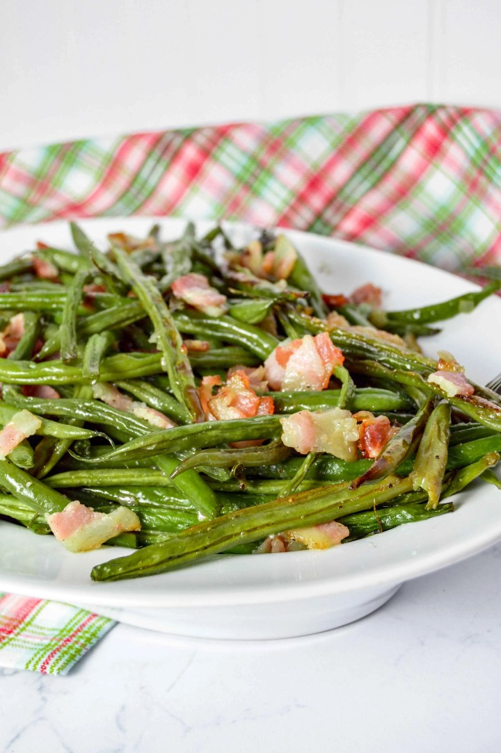Bacon Green Beans in a white oval bowl with a silver spoon sticking out on the right hand side.  The background is white with a red/white and green plaid towel. www.atwistedplate.com/bacon-green-beans/