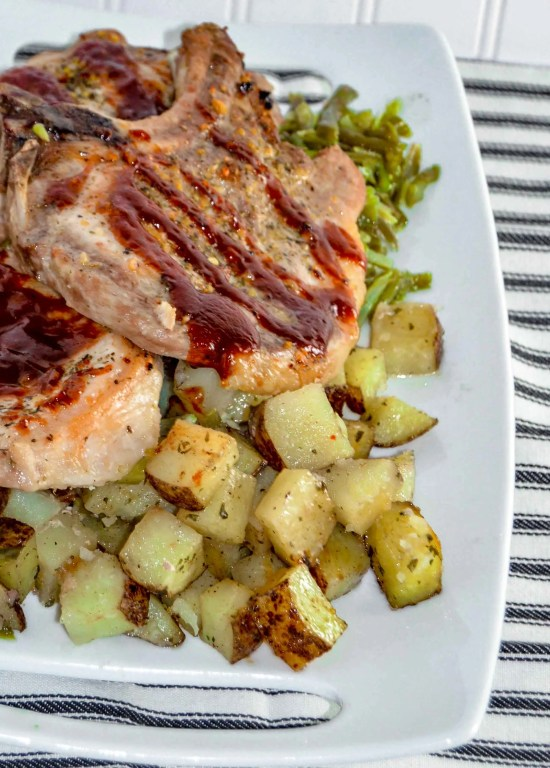 Angle close up view of a white rectangle dish with roasted potatoes, green beans and pork chops topped with bbq sauce.  Sheet Pan Pork Chop Dinner. www.atwistedplate.com/sheet-pan-pork-chop-dinner/