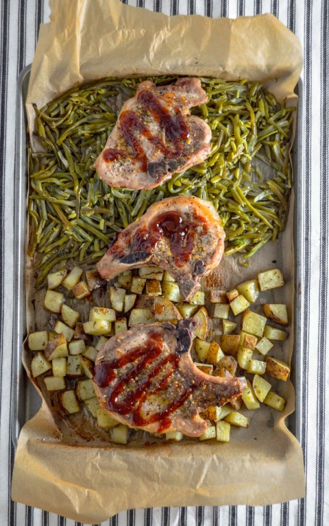 Vertical sheet pan with parchment paper.  on the bottom half is cubed potatoes, on the top half is green beans.  On top are three pork chops with BBQ Sauce on it.  Sheet Pan Pork Chop Dinner. www.atwistedplate.com/sheet-pan-pork-chop-dinner/