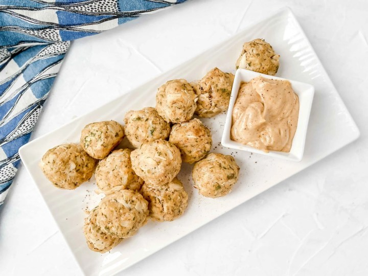 Image is a top angle view of Paleo Maryland Crab Ball on a white rectangle plate. There is a bow of Old Bay Aioli on the plate. The plate is on a gray background with a black and white dish towel on the left. www.atwistedplate.com/paleo-maryland-crab-balls/