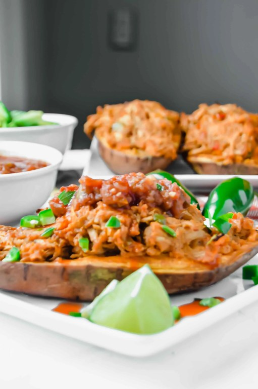 Side Image of chicken fajita stuffed sweet potato topped with jalapeños, hot sauce and salsa.  In the background there is a bowl  of salsa, avocado and a plate of chicken stuffed sweet potatoes. www.atwistedplate.com