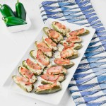 Bacon Jalapeno Bites on white rectangle plate with a blue and white towel and bowl of jalapeño www.atwistedplate.com