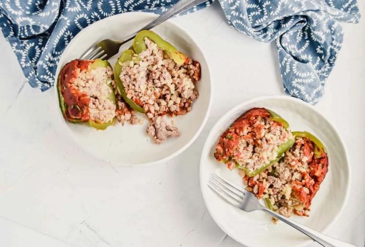 Image for Pork & Cauliflower Rice Stuffed Peppers of a cut open stuffed pepper in a white bowl. https://www.atwistedplate.com/pork-cauliflower-rice-stuffed-pepper/