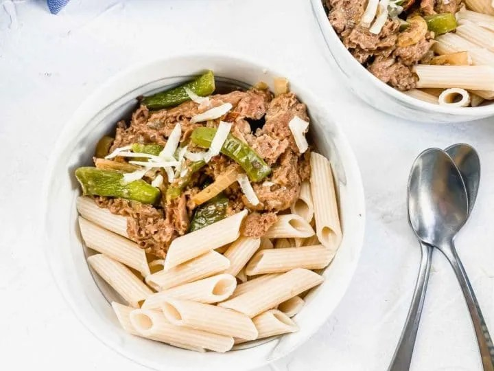 image is two bowls of pasta and cheesesteak with part of the pan with cheesesteak and a blue towel. www.atwistedplate.com/cheesesteak-pasta/