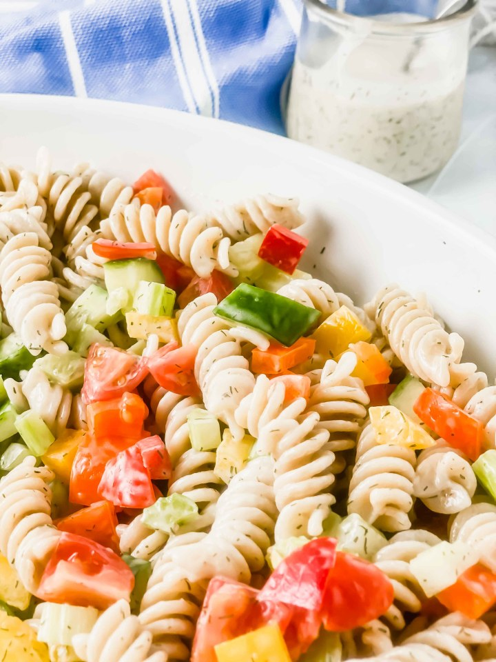 Image of Dill pasta salad in a white bowl. There is a jar of creamy dill pasta sauce and a spoon. At the top there blue bowl with a white towel. https://www.atwistedplate.com/dill-pasta-salad/