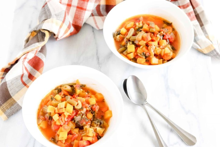 Two Bowls of Harvest Veggie Soup against a Marble background with two spoons stacked inbetween. Behind the bowls is fall colored plaid towel. https://www.atwistedplate.com/harvest-veggie-soup/