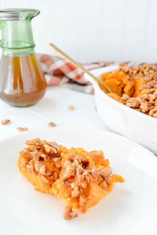 Top view images of MMaple & Walnut Sweet Potato Casserole in an oval backing dish with a fall colored plaid towel, maple syrup in a green jar and walnuts scattered around. Above in purple script it says Maple & Walnut Sweet Potato Bake. www.atwistedplate.com/paleo-maple-walnut-sweet-potato-casserole/