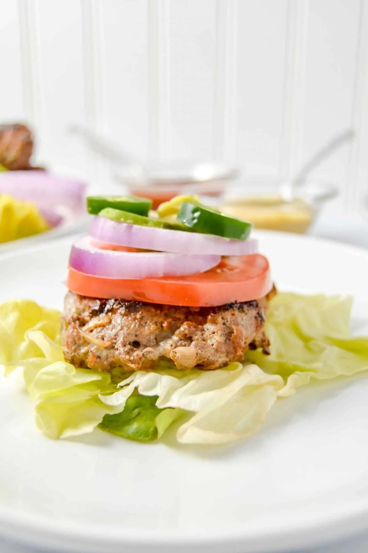 Image is a side view of a Ranch burger on top a bed of lettuce with a round white plate.  Atop the burger red onion, tomato, mustard, ketchup, jalapeño and avocado. There is a bowl of mustard and a bowl of ketchup above the plate.  Next to it is a cut off plate with burger and red onion.   www.atwistedplate.com/savory-ranch-burger/