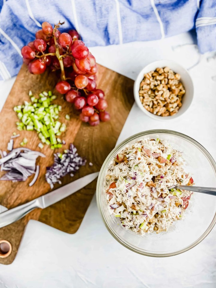 Side view of a bowl of Chicken Walnut and Grape Salad.. There is a blue and white towel, chopped red onions, celery and red grapes on a wood cutting board Walnuts along the bottom of the image. https://www.atwistedplate.com/chicken-walnut-and-grape-salad/