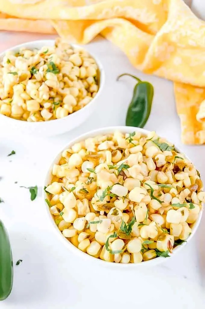 2 bowls of Corn Salad, corn, jalapeño and honey mixed together.  Jalapeno and a yellow towel in the background.  www.atwistedplate.com/corn-salad/