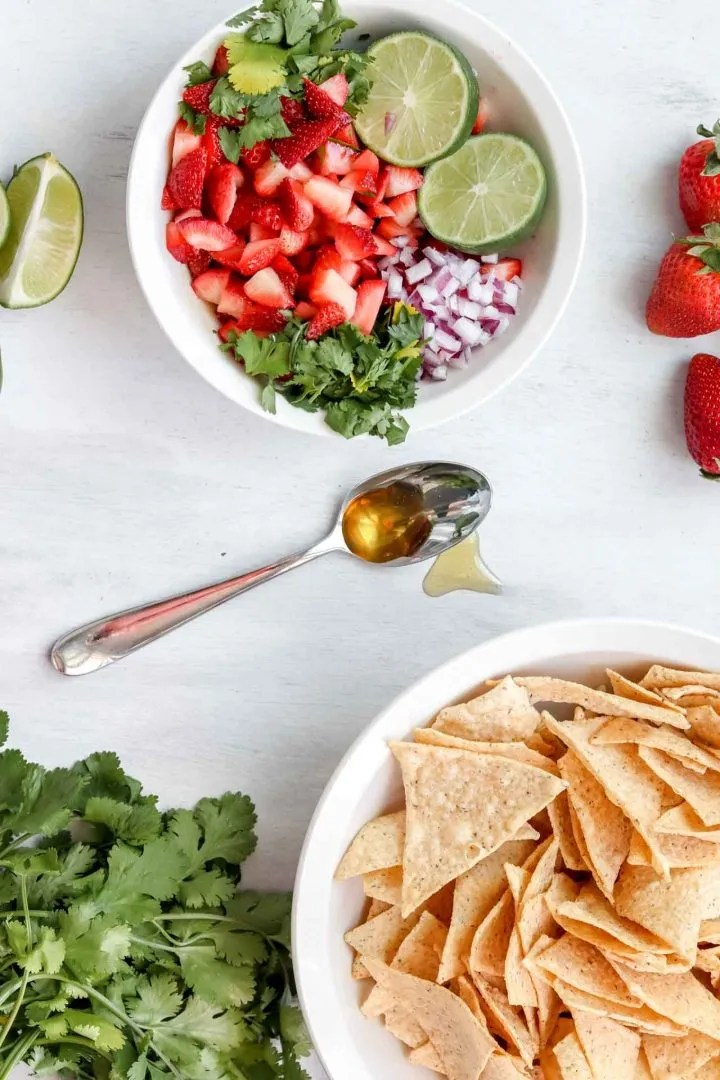 strawberry salsa image is strawberry salsa in a bowl, spoon with honey on it, a bowl of chips, cilantro and strawberries.  www.atwistedplate.com/strawberry-salsa/