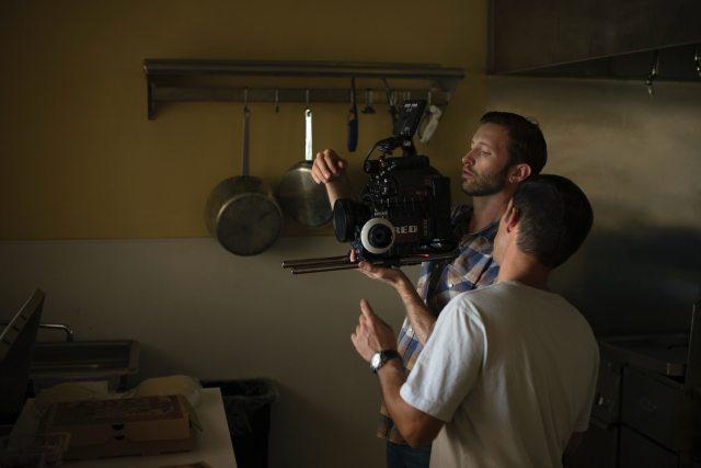 wo men fixing camera in kitchen