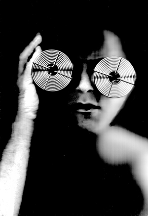 A photo of a blurred face with metal glasses in black and white