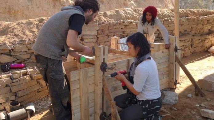 """Nitzan Iserovitch von der Back to Earth Community, links, lehrt nepalesische Frauen, eine """"Stampferde""""-Verschalung zu bauen. Foto Facebook."""