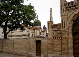 Links im Hintergrund die Synagoge von Halle; im Vordergrund der Eingang zum jüdischen Friedhof. Foto Allexkoch, CC BY-SA 4.0, https://commons.wikimedia.org/w/index.php?curid=42881121