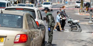 Grenzschutzpolizistin die in der Stadt Bnei Brak vorbeifahrende Autofahrer kontrolliert und die Mobilitätsbeschränkungen durchsetzt. 3. April 2020. Foto Kobi Richter/TPS