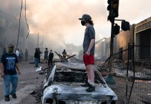 Ausschreitungen in Minneapolis am 28. Mai 2020. Foto Lorie Shaull, St Paul, United States - A man stands on a burned out car on Thursday morning as fires burn behind him in the Lake St area of Minneapolis, Minnesota, CC BY-SA 2.0, https://commons.wikimedia.org/w/index.php?curid=90742413