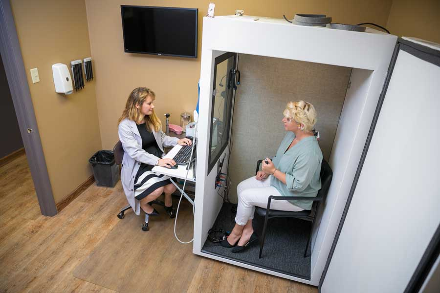 liz meyer, au.d. guiding a patient through a hearing test in a sound booth